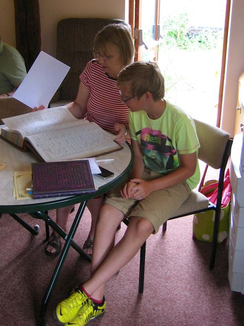 Fraser and his grandmother, Pauline, searching through the Burial Book.